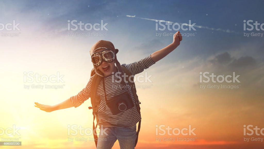 child is playing at sunset stock photo