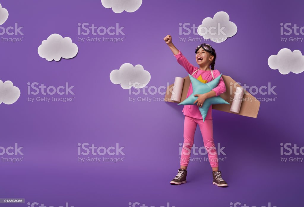 child is playing superhero Little child girl in an astronaut costume is playing and dreaming of becoming a spaceman. Portrait of funny kid on a background of ultraviolet wall with white clouds. Child Stock Photo