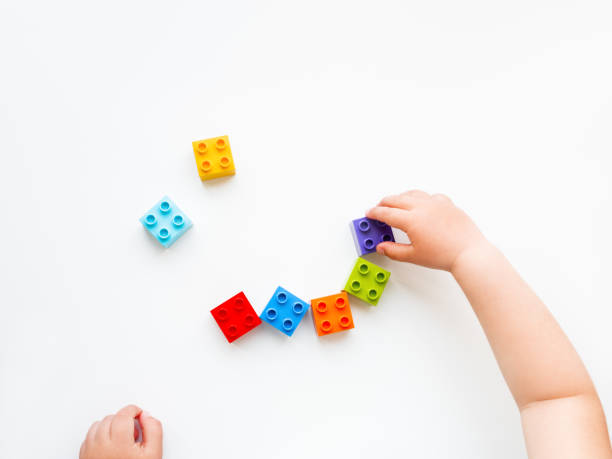 Child is playing with colorful constructor blocks. Kid's hands with bricks toy on white background. Educational toy, flat lay, top view. stock photo