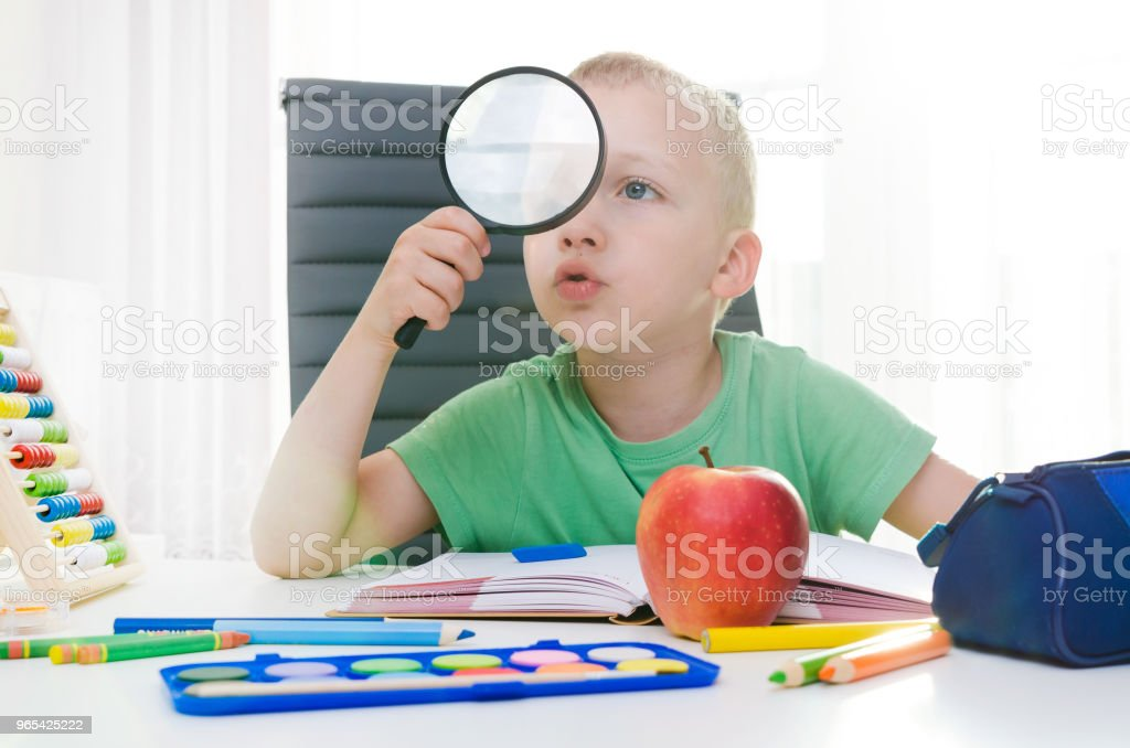 Child is playing with magnifying glass royalty-free stock photo