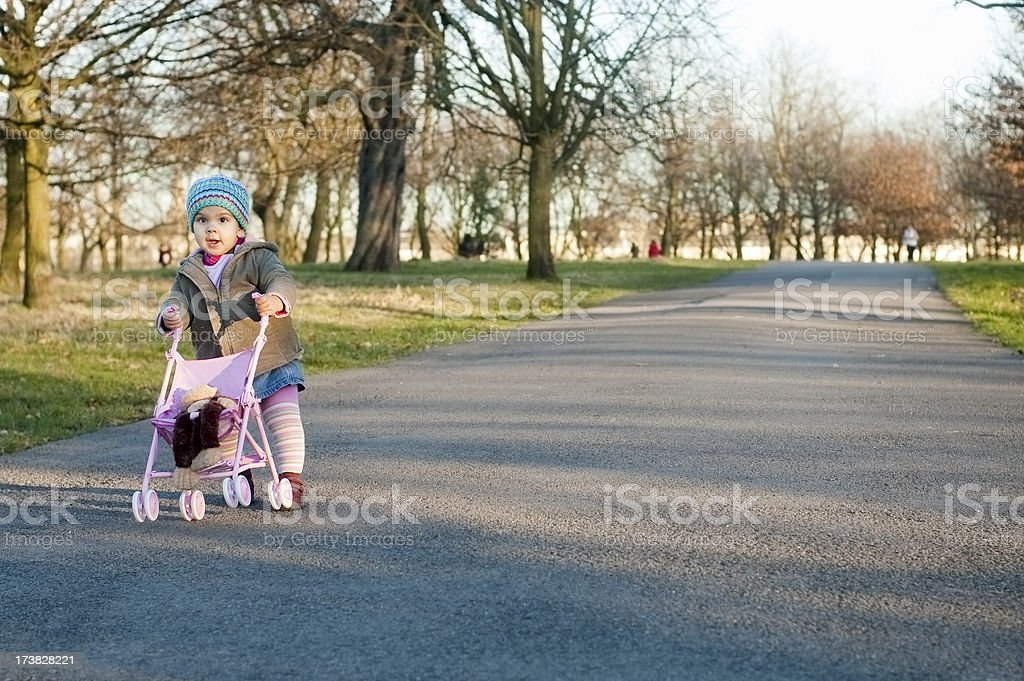 Child is Pushing Toy Stroller in Park, Horizontal royalty-free stock photo