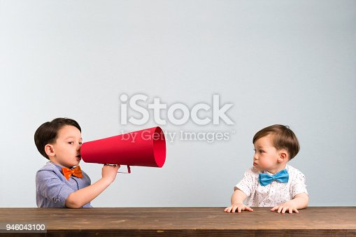 623763462istockphoto Child is shouting through megaphone to another child 946043100