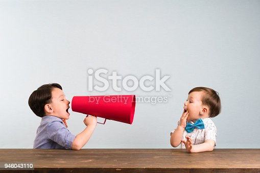 623763462istockphoto Child is shouting through megaphone to another child 946043110