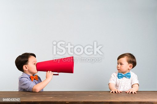 623763462istockphoto Child is shouting through megaphone to another child 946043242