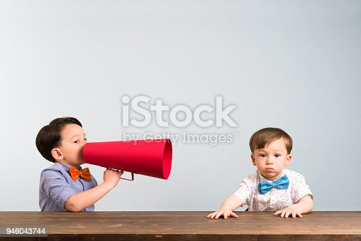 623763462istockphoto Child is shouting through megaphone to another child 946043744