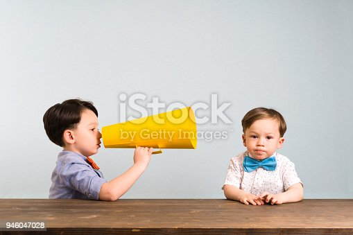 623763462istockphoto Child is shouting through megaphone to another child 946047028