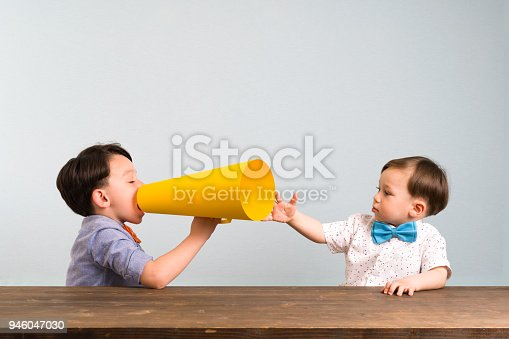 623763462istockphoto Child is shouting through megaphone to another child 946047030