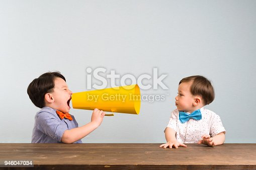 623763462istockphoto Child is shouting through megaphone to another child 946047034