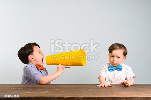 623763462istockphoto Child is shouting through megaphone to another child 946047406