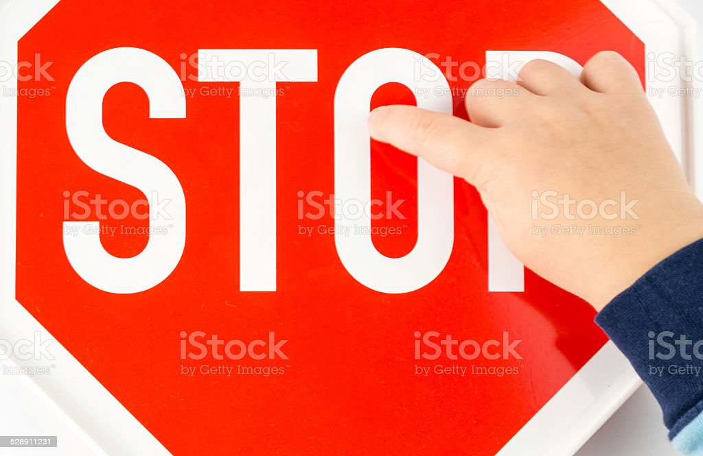 child is showing on stop sign with his finger stock photo