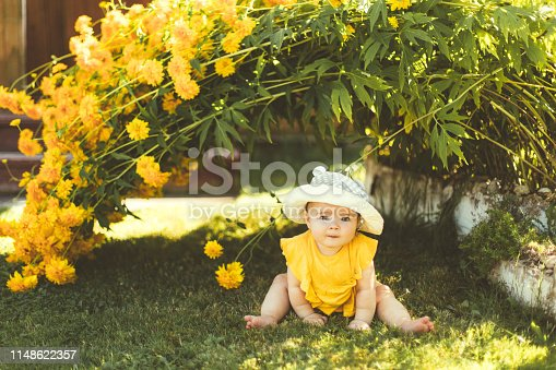 A child is sitting in the garden under a large yellow bush of flowers. A little girl in a yellow dress and hat learns nature, the summer sun, green grass, a blurred background.