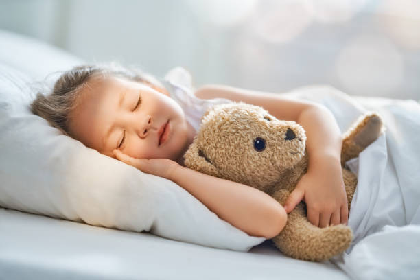 child is sleeping in the bed stock photo