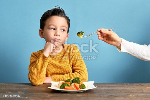 Child is very unhappy with having to eat vegetables. There is a lot of vegetables on his plate. He hates vegetables.