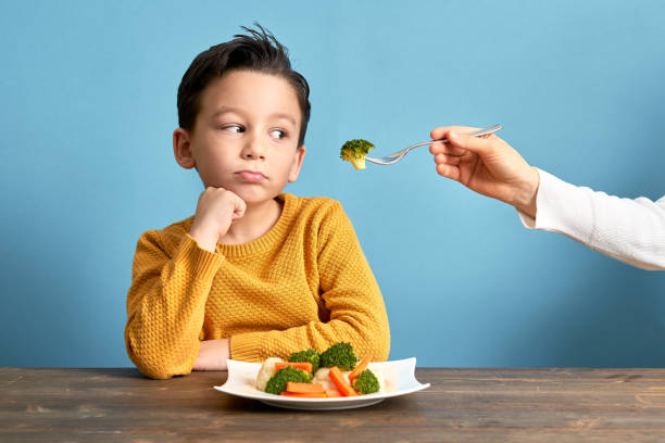 Child is very unhappy with having to eat vegetables. stock photo