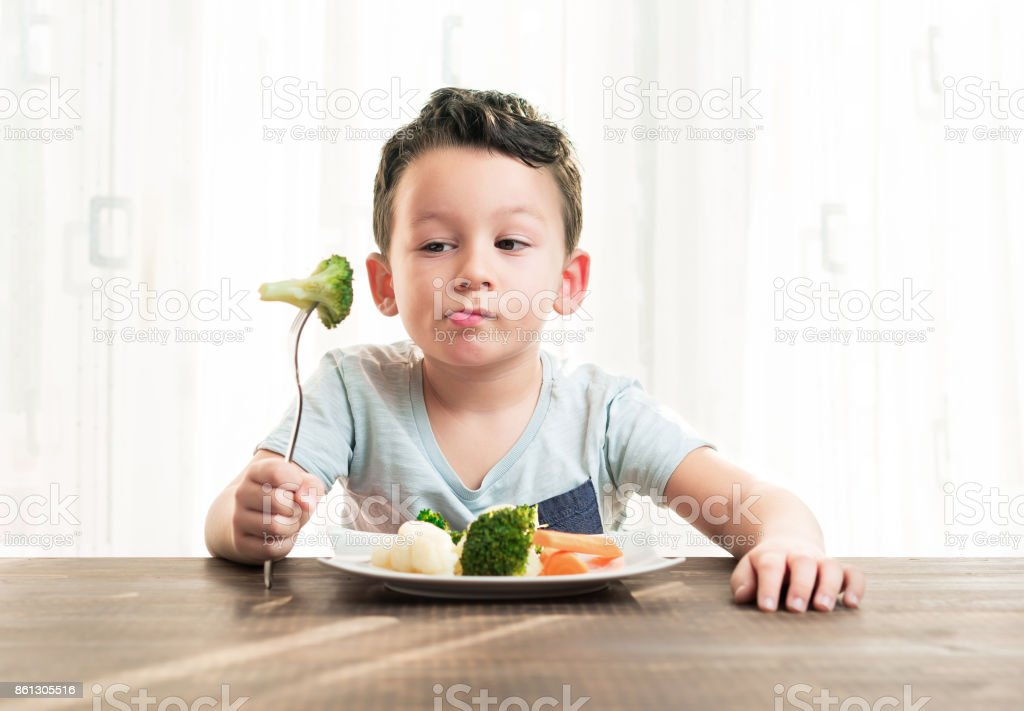 Child is very unhappy with having to eat vegetables. - foto stock