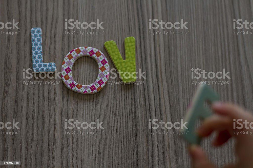Niño está escrito palabra Love de juguete letras coloridas saliendo foto de stock libre de derechos