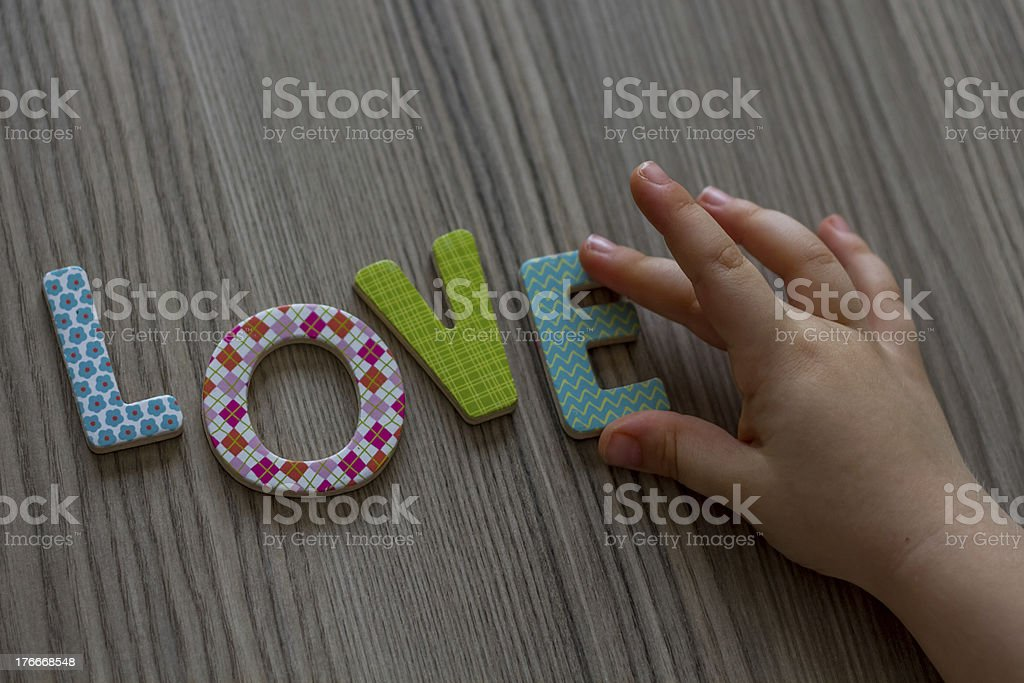 Child is Writing Word Love From Colourful Toy Letters royalty-free stock photo