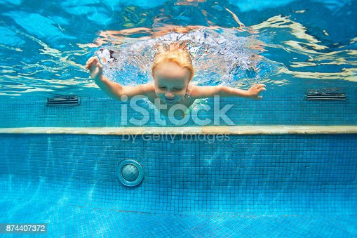 istock Child jump underwater into swimming pool 874407372