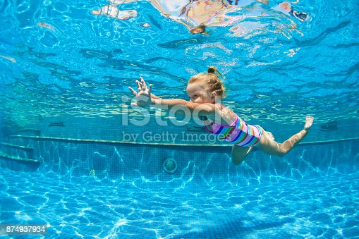 istock Child jump underwater into swimming pool 874937934