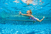 Funny portrait of child learn swimming, diving in blue pool with fun - jumping deep down underwater with splashes. Healthy family lifestyle, kids water sports activity, swimming lesson with parents.