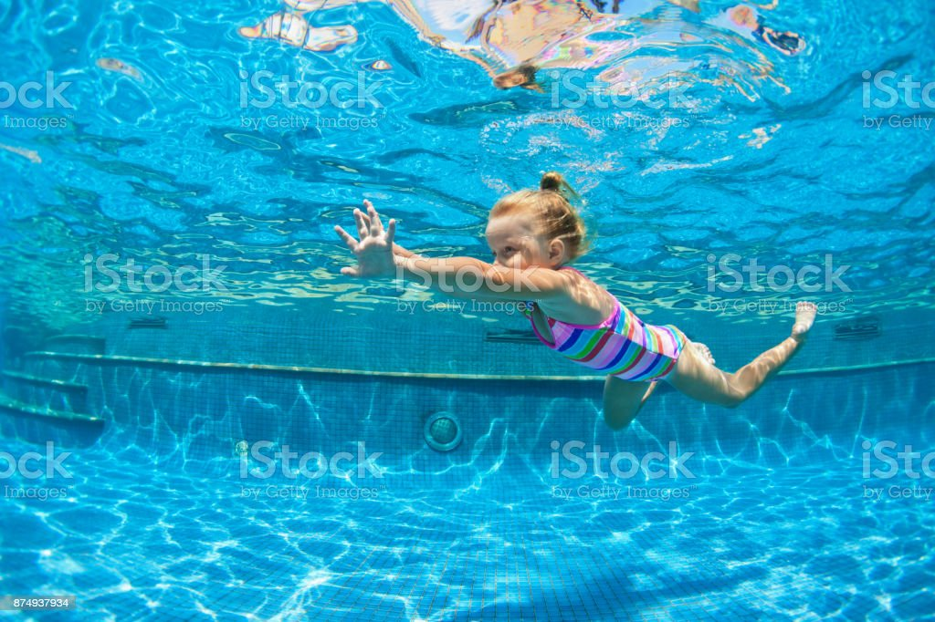 Child jump underwater into swimming pool stock photo