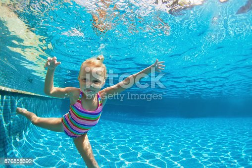 istock Child jump underwater into swimming pool 876858392