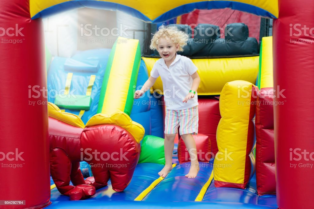 Child jumping on playground trampoline. Kids jump. stock photo