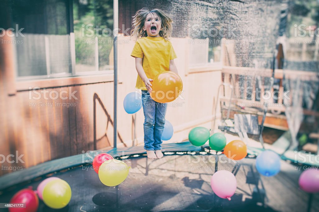 Child jumps on trampoline laughing with balloons stock photo