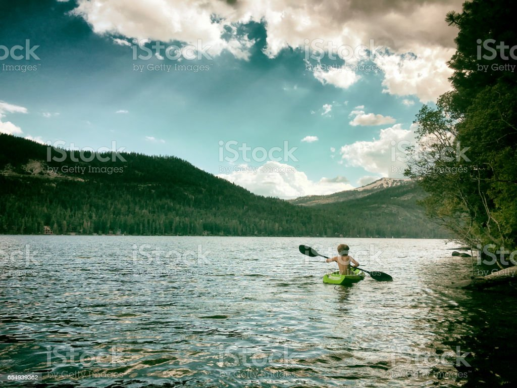 Child Kayaking alone on a big mountain lake stock photo