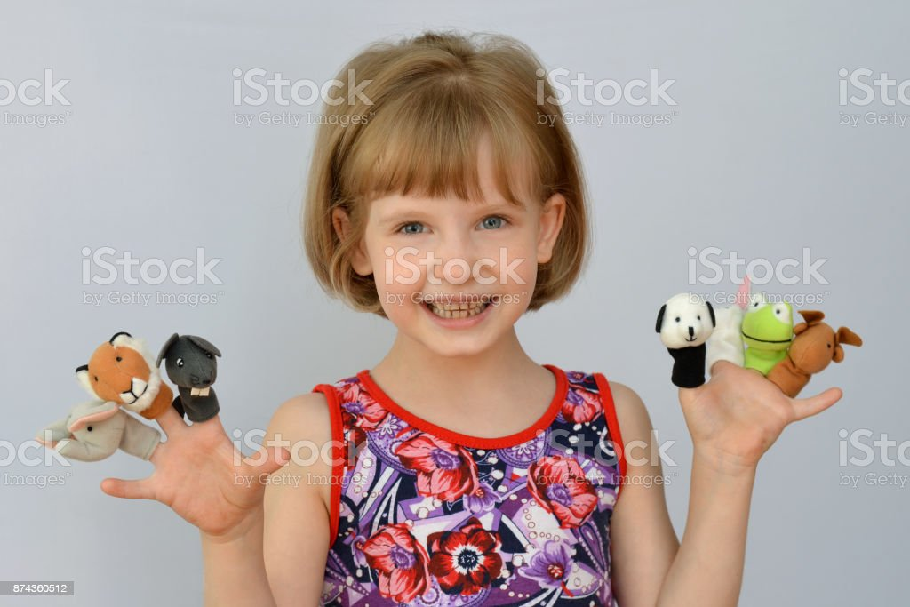 child, kid,(little girl) playing  with toy dolls is wearing on the fingers stock photo