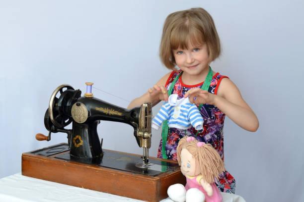 kind, kind,(little girl) schneiderin näht kleider für die puppen auf die alte nähmaschine - schnittmuster kinder stock-fotos und bilder