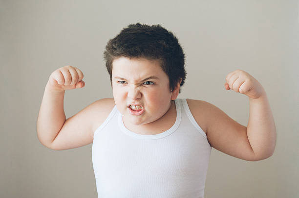 child kid showing muscles exercise  teeth stock photo