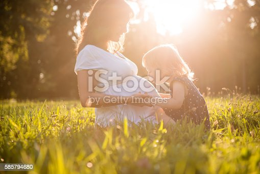 Little child kissing belly of her mother outdoor in sunny nature