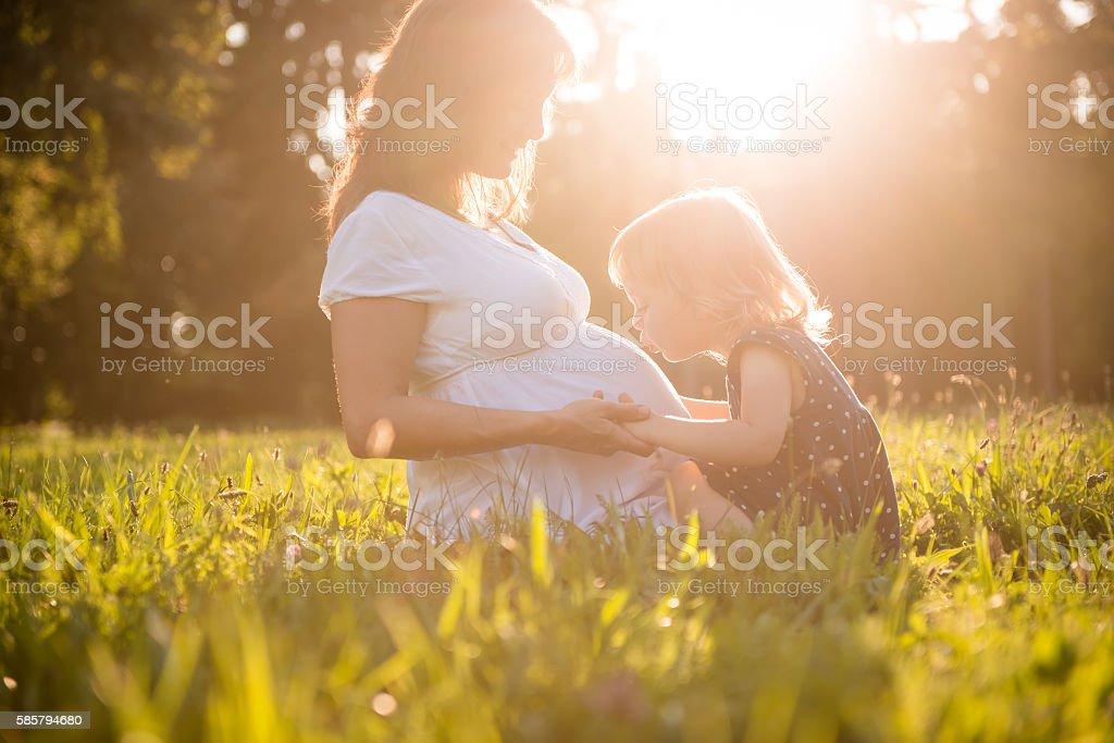Child kissing belly og pregnant mother stock photo