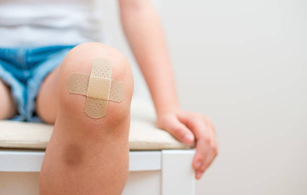 Child knee with an adhesive bandage and bruise. stock photo