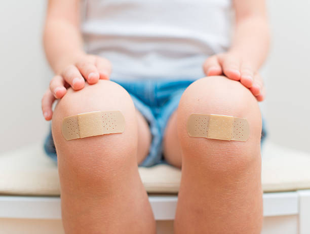 Child knee with an adhesive bandage. stock photo