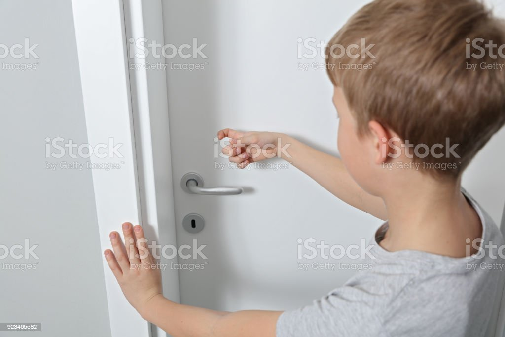 Child knocking on door before entering, home privacy concept stock photo