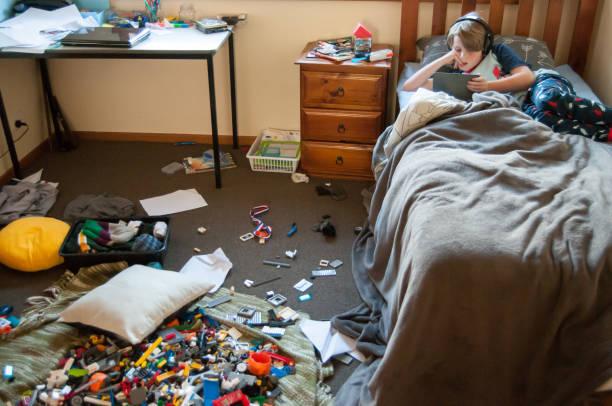 kind im bett auf elektronisches gerät mit einem sehr unordentlich zimmer - schlafzimmer teenager stock-fotos und bilder