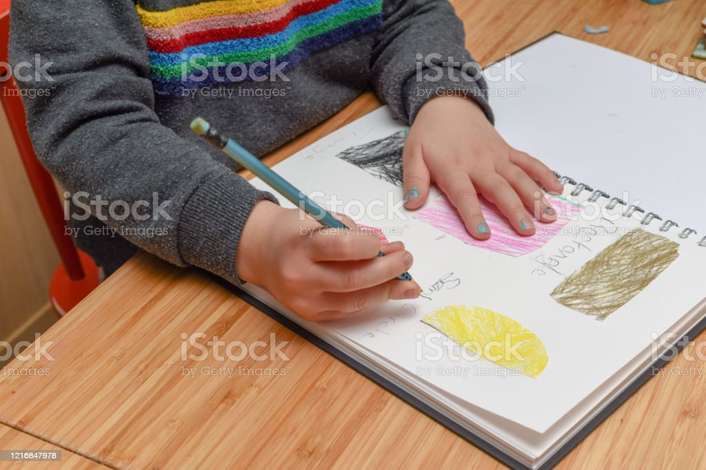 Child learning at home. Pre school age child learning about shapes and hand writing Child learning at home. Pre school age child learning about shapes and hand writing Book Stock Photo
