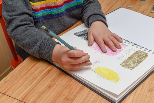 Child Learning At Home Pre School Age Child Learning About Shapes And Hand Writing Stock Photo - Download Image Now
