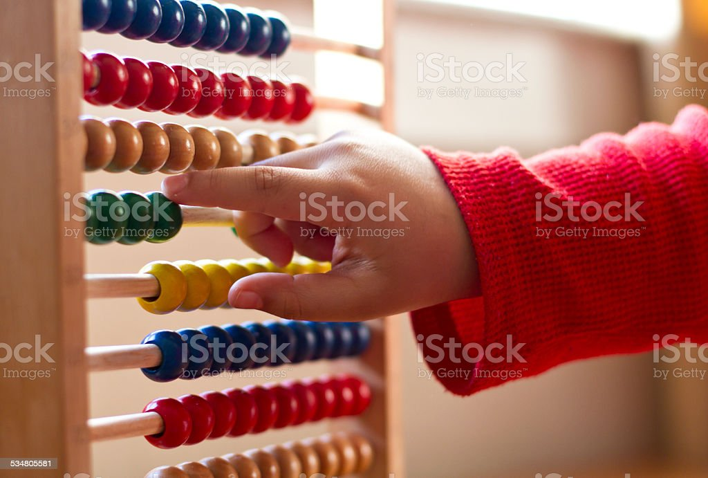 Child learning counts on Abacus stock photo
