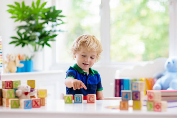 Child learning letters. Kid with wooden abc blocks Child learning letters and numbers. Kid with colorful wooden abc blocks. Little boy spelling words with educational block toys. Kids doing school homework at white desk. Bedroom for preschool children spelling stock pictures, royalty-free photos & images