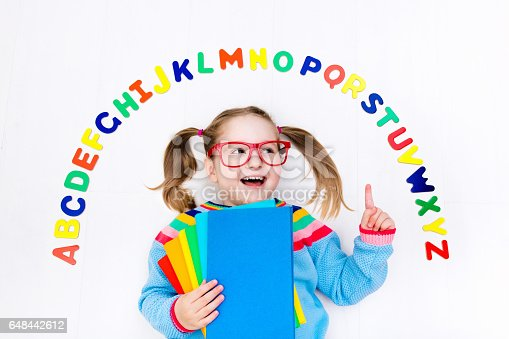 istock Child learning letters of alphabet and reading 648442612