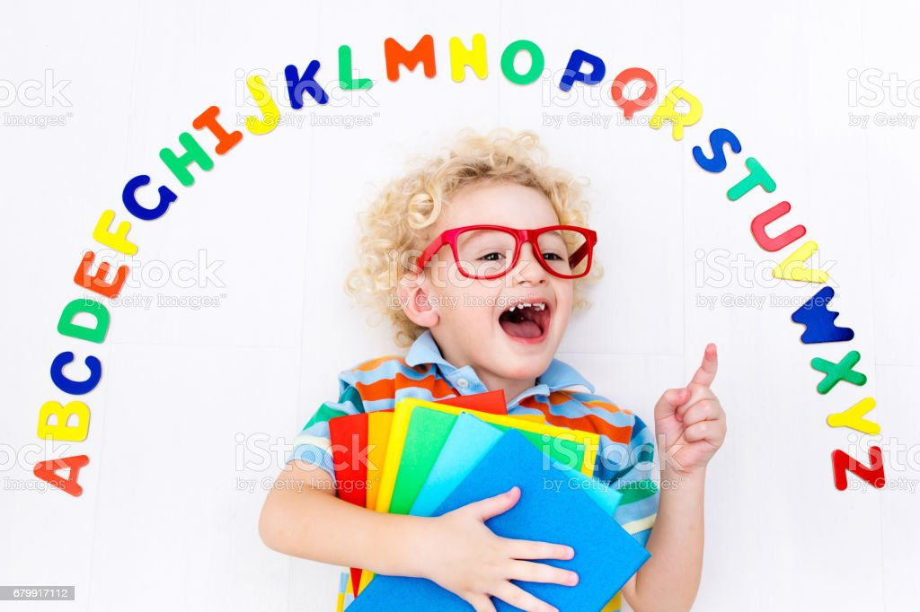 Child learning letters of alphabet and reading stock photo