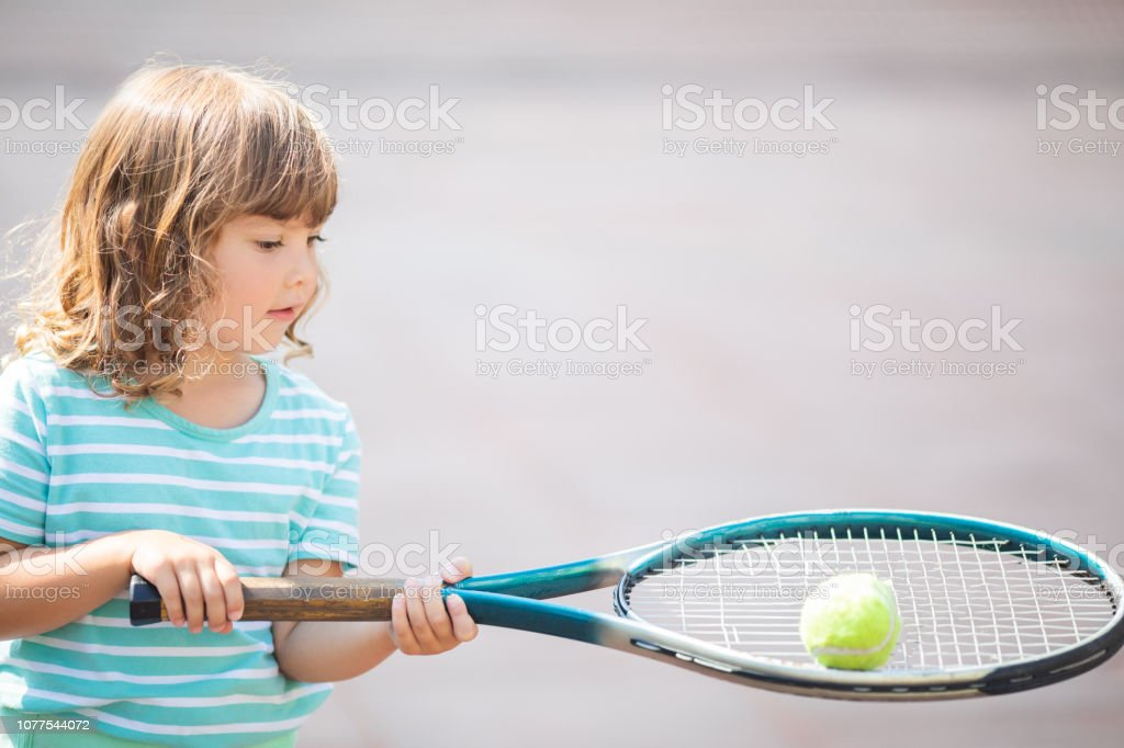 Child learning to play tennis on outdoor court. Little girl with...