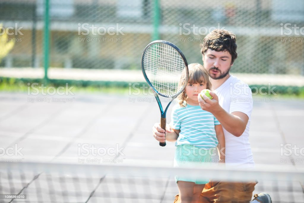 A child learns to play tennis with his father in the open courtyard....