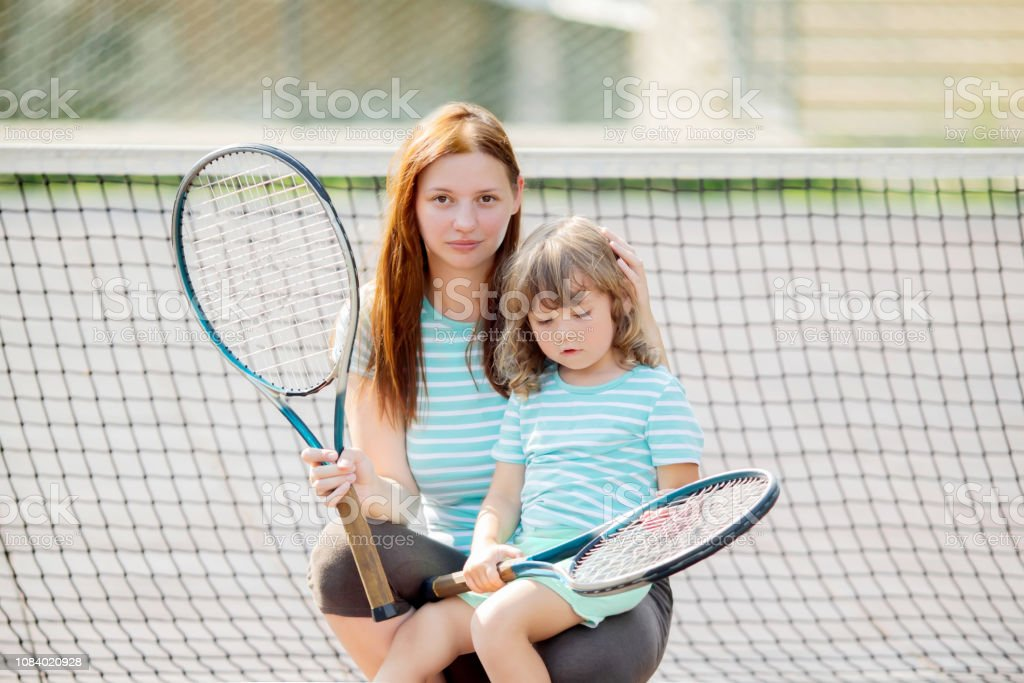 Child learning to play tennis with her mother on outdoor court....