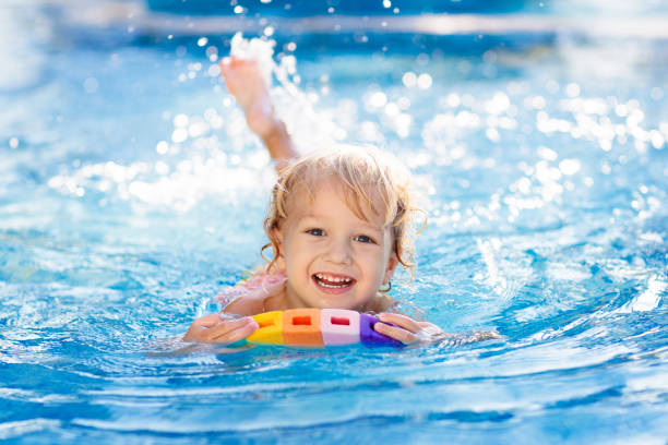 child learning to swim. kids in swimming pool. - swimming stock pictures, royalty-free photos & images