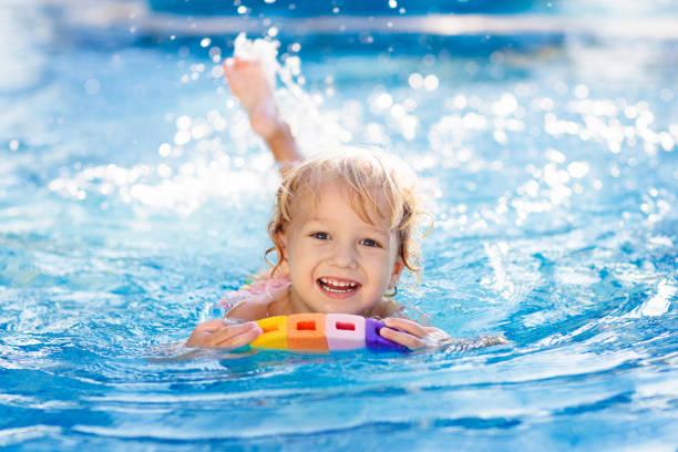 niño aprendiendo a nadar. niños en la piscina. - natación fotografías e imágenes de stock