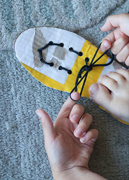 Child learning to tie shoe laces stock photo